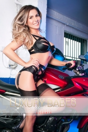A speed freak, Nataly is pictured in front of a red motorbike whilst in sexy black lingerie